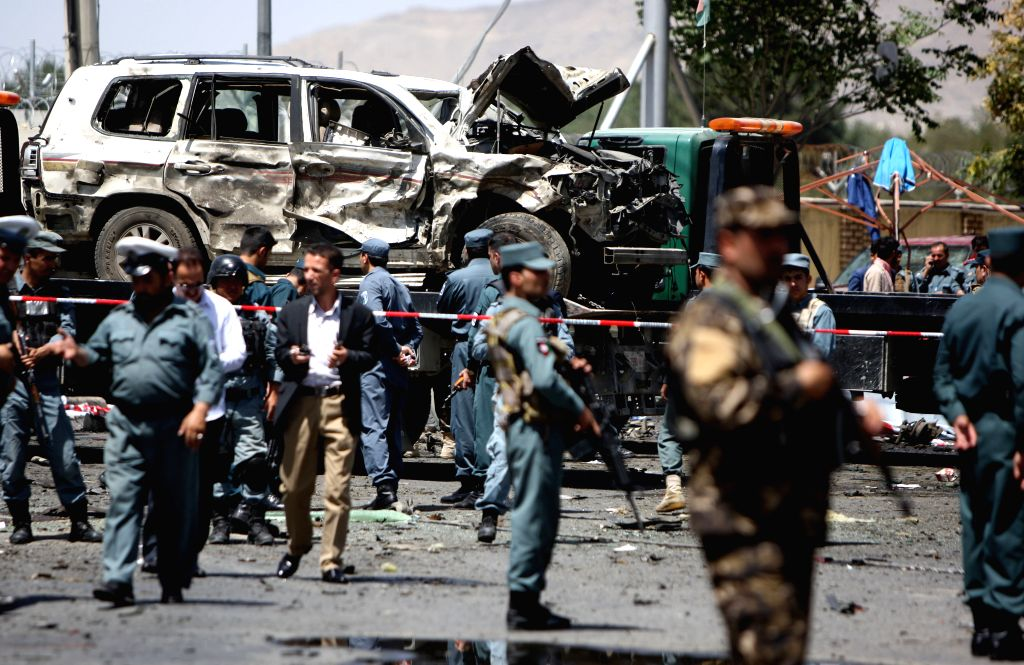 Afghan policemen inspect the site of a suicide car bombing in Kabul, Afghanistan, Aug. 10, 2015. At least four people were killed and 15 others wounded after a ...