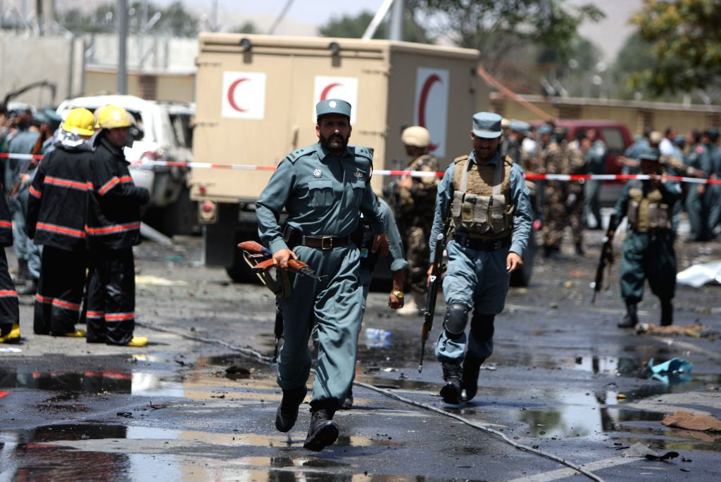 Afghan policemen run at the site of a suicide car bombing in Kabul, Afghanistan, Aug. 10, 2015. At least four people were killed and 15 others wounded after a suicide ...