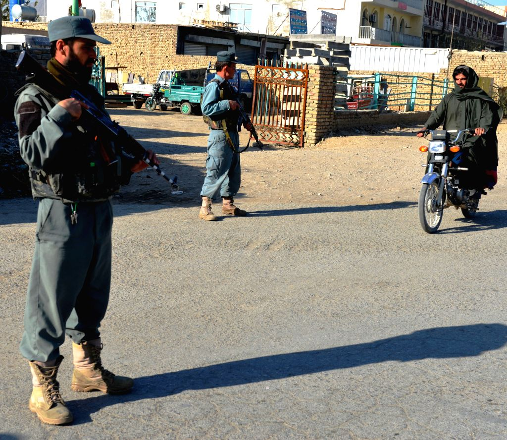 Afghan policemen stand guard at a police checkpoint in Kandahar province of southern Afghanistan, Nov. 21, 2015.