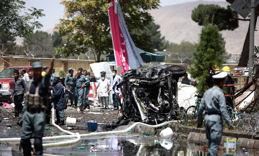 Afghan security forces gather around a destroyed vehicle at the site of a suicide car bombing in Kabul, Afghanistan, Aug. 10, 2015. At least four people were killed ...