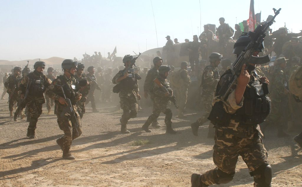 Afghan soldiers run towards their military vehicles at a military camp in Faryab Province, north Afghanistan, Aug. 5, 2015. Units of Afghan national police backed by ...