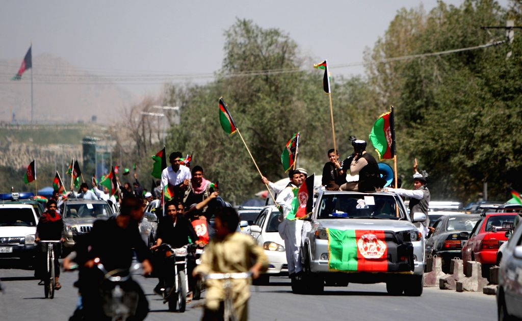 Afghans hold Afghanistan national flags to celebrate the country's 96th anniversary of independence from the British empire occupation in Kabul, Afghanistan, Aug. 19, ...