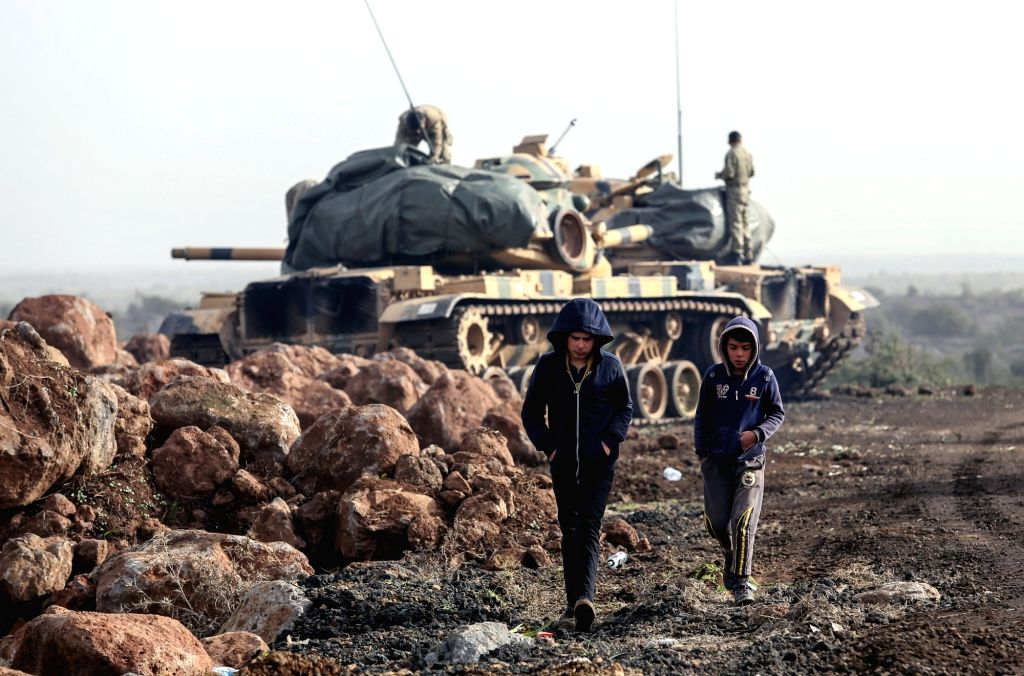 """AFRIN (SYRIA)Two boys walk by Turkish army tanks in Afrin, Syria, on Jan. 22, 2018. Turkey launched on Jan. 20 a new operation dubbed as """"Operation Olive ..."""