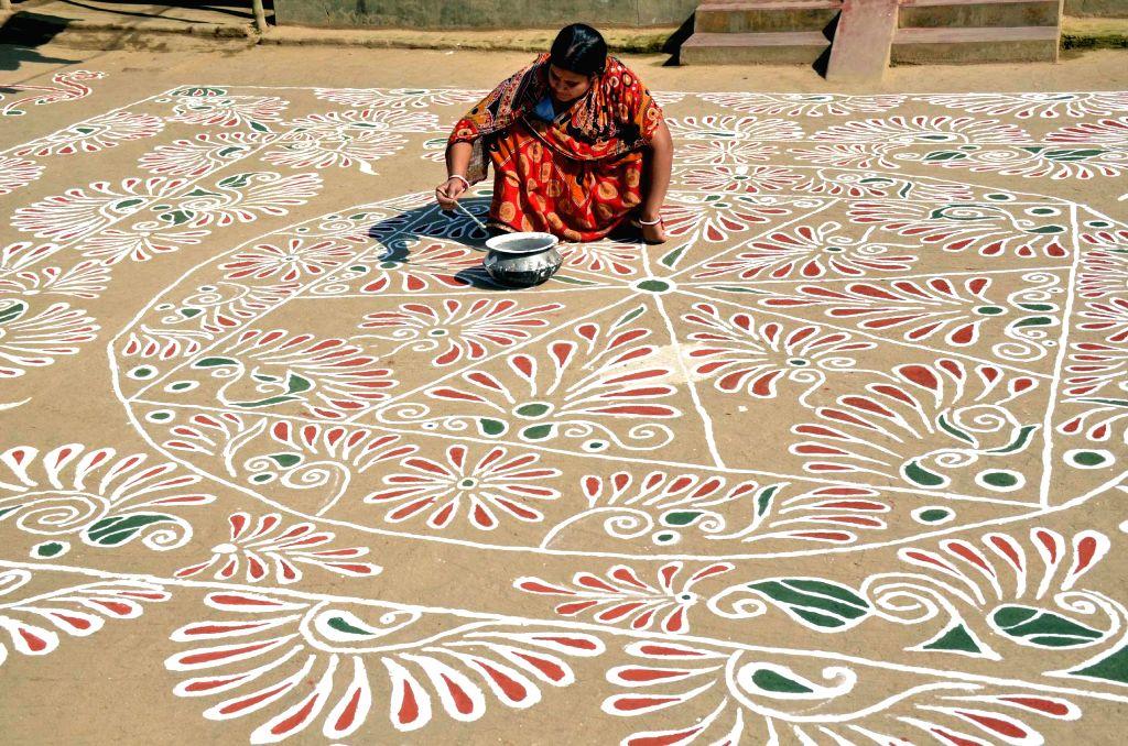 A woman makes a `Rangoli` on Makar Sankranti in Lankamura village situated on the outskirts of Agartala on Jan 14, 2015.