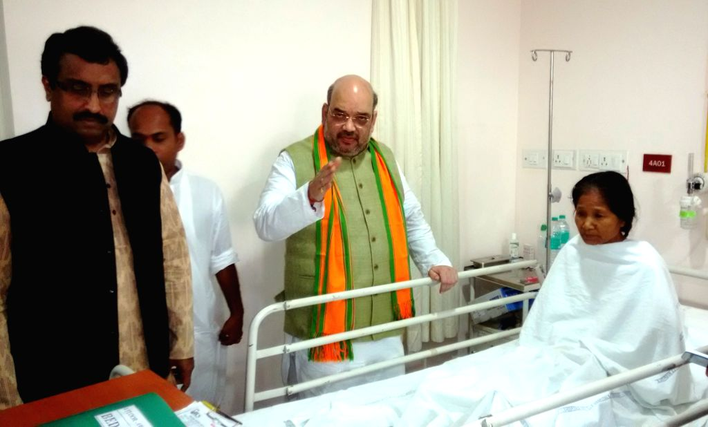 BJP chief Amit Shah meets a woman who is undergoing treatment at a hospital after getting injured in police firing, in Agartala April 27, 2015. She was participating in a demonstration to ...