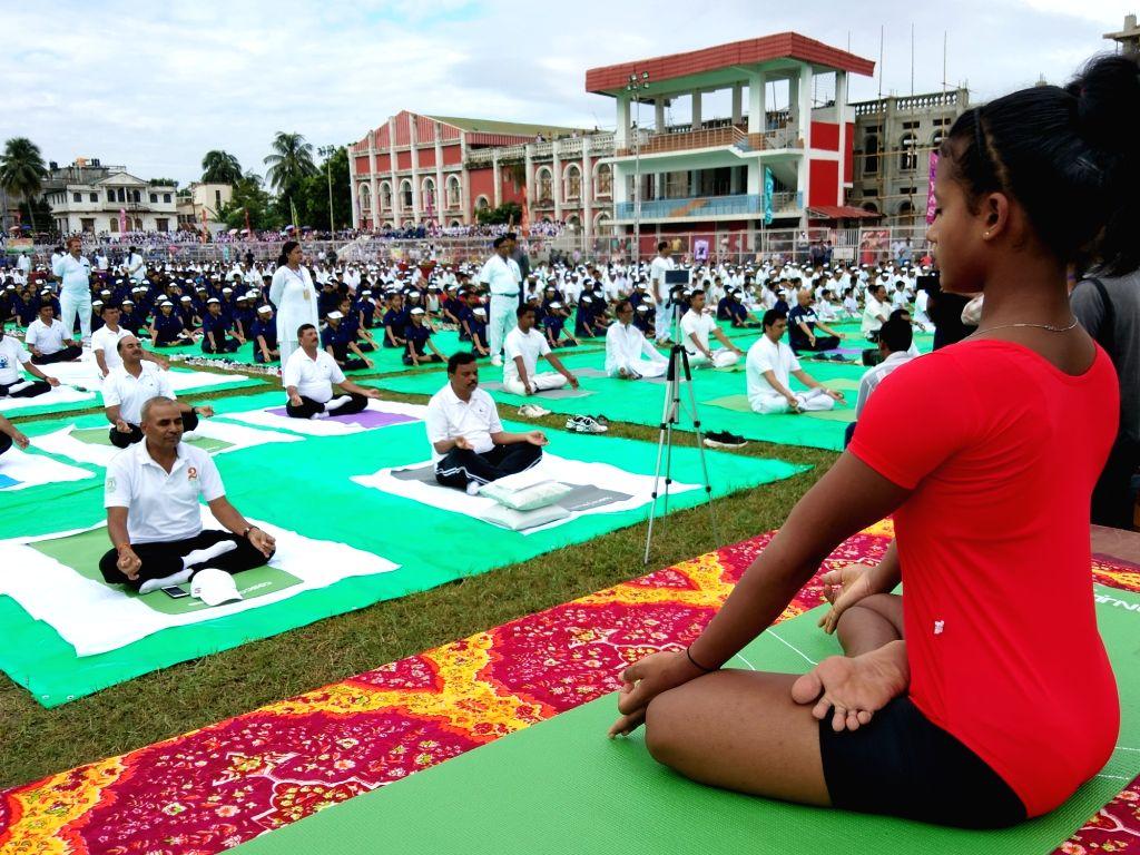 Agartala: People practice yoga asanas -postures- on International Yoga Day 2019 at Umakanta Mini Stadium in Agartala on June 21, 2019. (Photo: IANS)