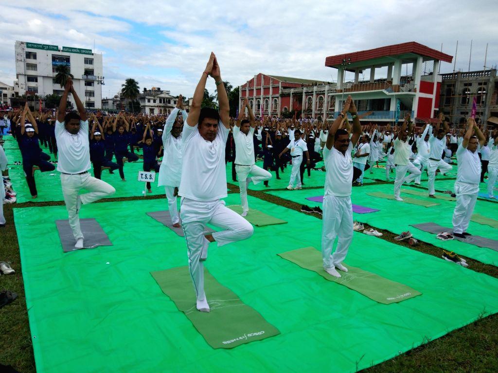 Agartala: Tripura Chief Minister Biplab Kumar Deb practices yoga asanas -postures- on International Yoga Day 2019 at Umakanta Mini Stadium in Agartala on June 21, 2019. (Photo: IANS) - Biplab Kumar Deb