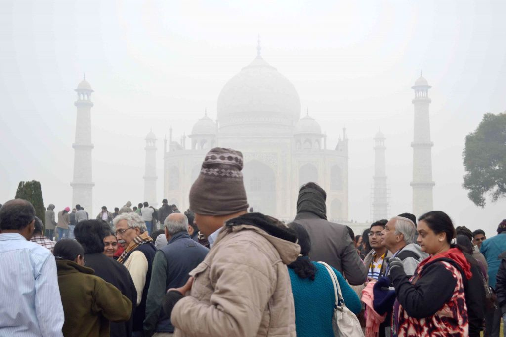 People throng the Taj Mahal on a foggy day in Agra on Dec 30, 2014.