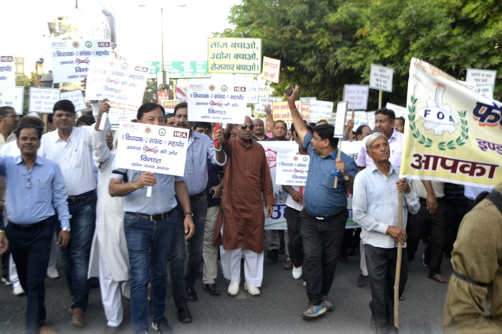 : Agra: Workers, industrialists and social activists carrying placards and banners protest against the restrictions on industries in the eco-sensitive Taj Trapezium Zone spread over 10,400 sq.km.; ...