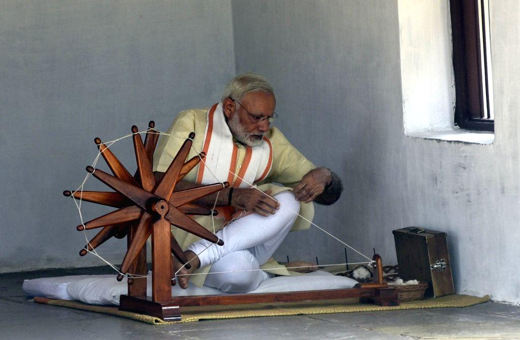 Ahmedabad: Prime Minister Narendra Modi sits beside a charkha - spinning wheel at Sabarmati Ashramin Ahmedabad on June 29, 2017. (Photo: IANS) - Narendra Modi