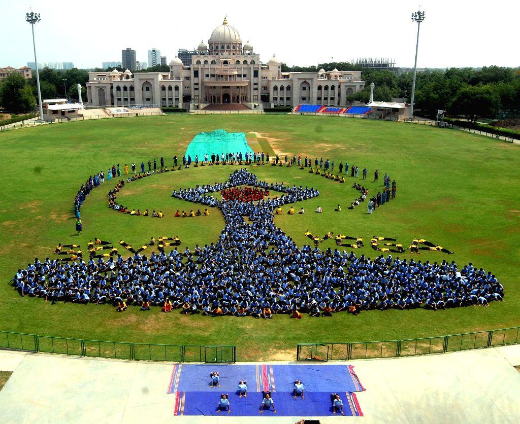 School students make a formation of Internation Yoga day logo during a rehearsal ahead of International Yoga Day at Swaminarayan Gurukul School in Ahmedabad on June 19, 2015.