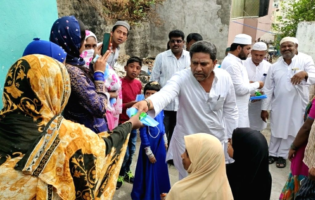 AIMIM leaders distribute masks and soaps among people besides spreading awareness among them on COVID-19 amid coronavirus pandemic, in Hyderabad on March 20, 2020.