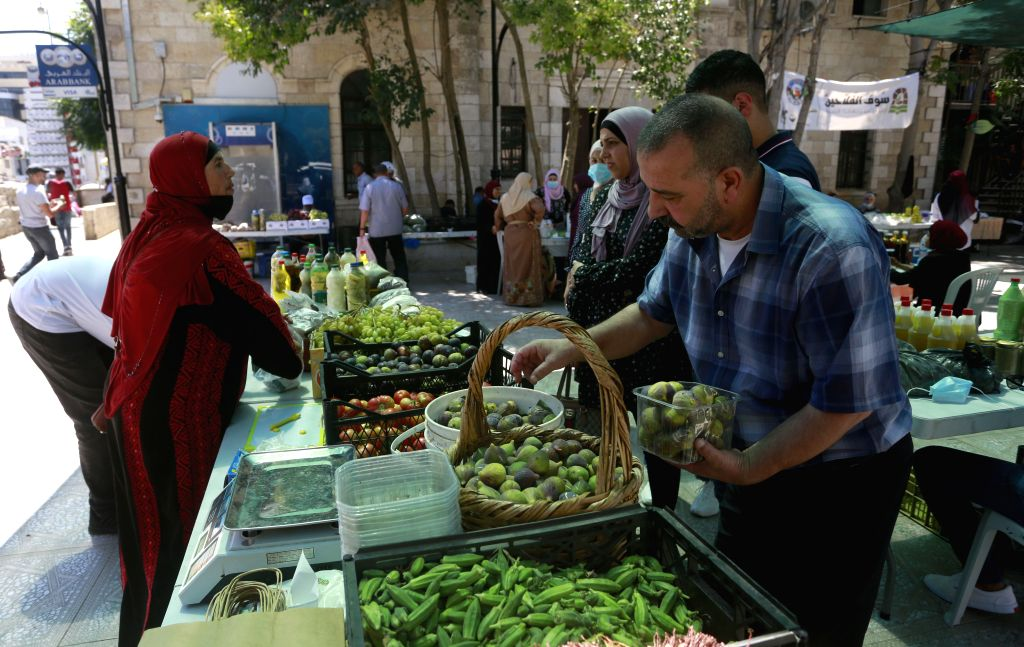 """Al-People visit the """"peasants market"""" in the West Bank city of Al-Bireh, on Aug. 29, 2020. TO GO WITH: """"Feature: Palestinian women earn money by ..."""