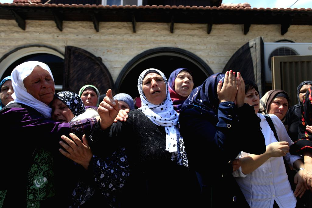 AL-Relatives of Palestinian Mahmoud Shawamreh, 21, mourn during his funeral in the West Bank town of Al-Ram, on July 22, 2014. Shawamreh was killed by an Israeli ...