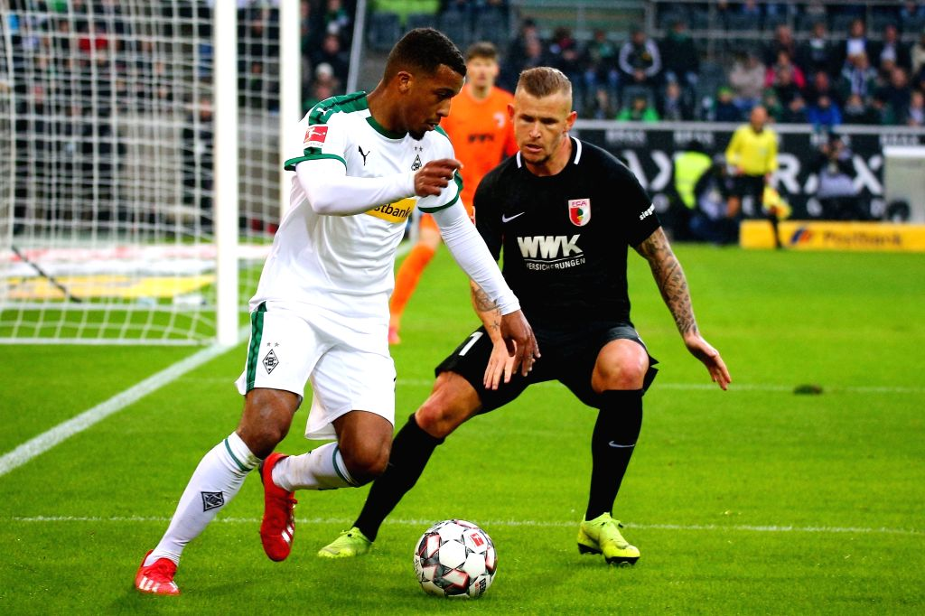 Alassane Plea (L) of Moenchengladbach vies with Jonathan Schmid of Augsburg during the Bundesliga match between Borussia Moenchengladbach and FC Augsburg ...