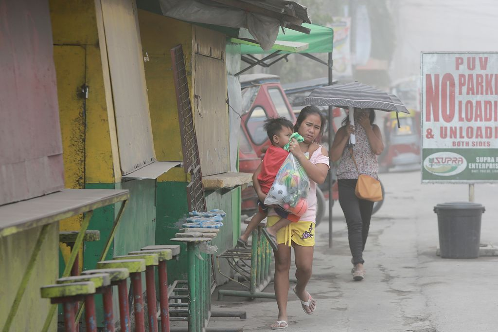ALBAY, Jan. 24, 2018 - Residents cover their noses as the ash spewed by Mount Mayon volcano hit Albay Province, the Philippines, Jan. 24, 2018. Mount Mayon volcano in the Philippines continued to ...