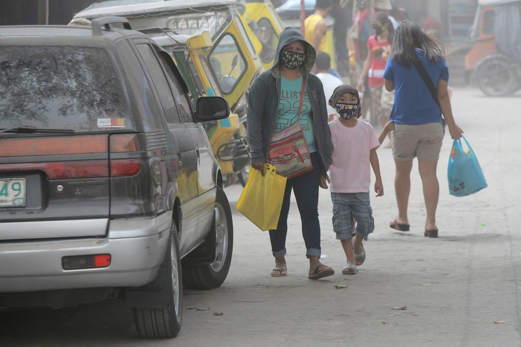 ALBAY, Jan. 24, 2018 - Residents wear masks as the ash spewed by Mount Mayon volcano hit Albay Province, the Philippines, Jan. 24, 2018. Mount Mayon volcano in the Philippines continued to spew lava ...