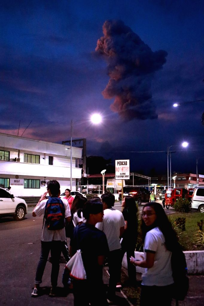 ALBAY, Jan. 24, 2018 - Students watch the ash plumes from Mayon volcano in Albay Province, the Philippines, Jan. 24, 2018. Mount Mayon volcano in the Philippines continued to spew lava and huge ...