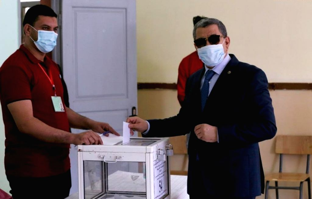 Algerian Prime Minister Abdelaziz Djerad (Front) picks up a ballot as he prepares to vote for the parliamentary elections at a polling station in Algiers, Algeria, on June 12, 2021. - Abdelaziz Djerad