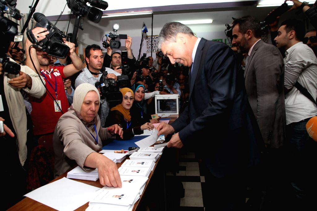 Algerian presidential candidate and former premier Ali Benflis (3rd R) prepares to cast his ballot at a polling center in Algiers, capital of Algeria, on April 17,