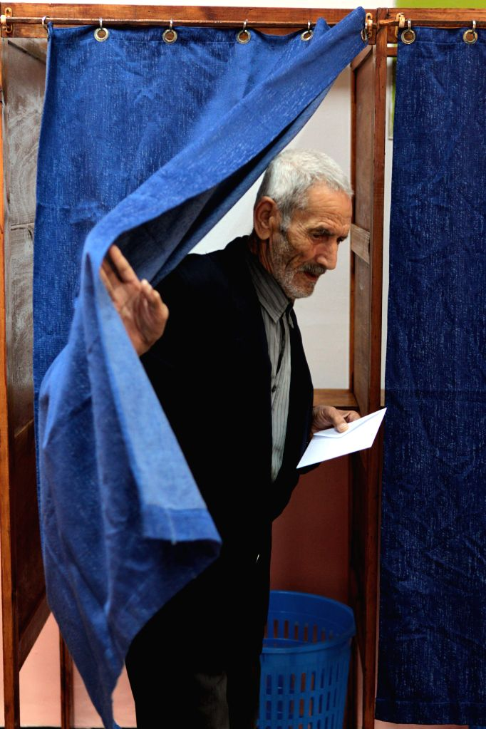 An Algerian man prepares to vote at a polling centre in Algiers on April 17, 2014. Algerian voters started casting ballots Thursday morning in the country's ... - Ali Benflis