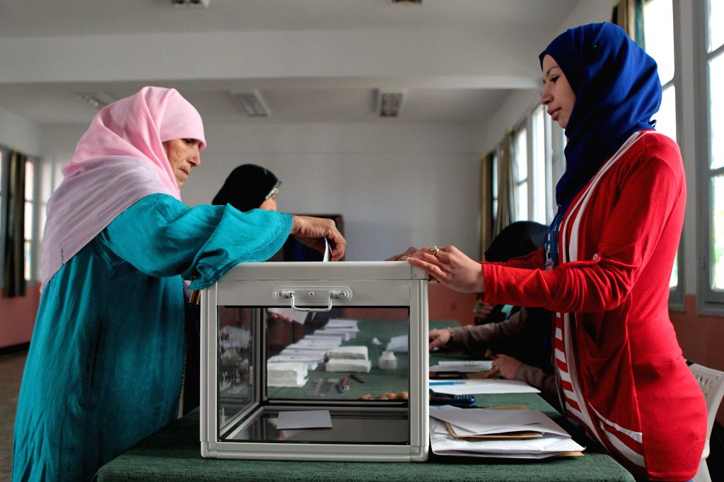 An Algerian woman casts her vote at a polling centre in Algiers on April 17, 2014. Algerian voters started casting ballots Thursday morning in the country's ... - Ali Benflis