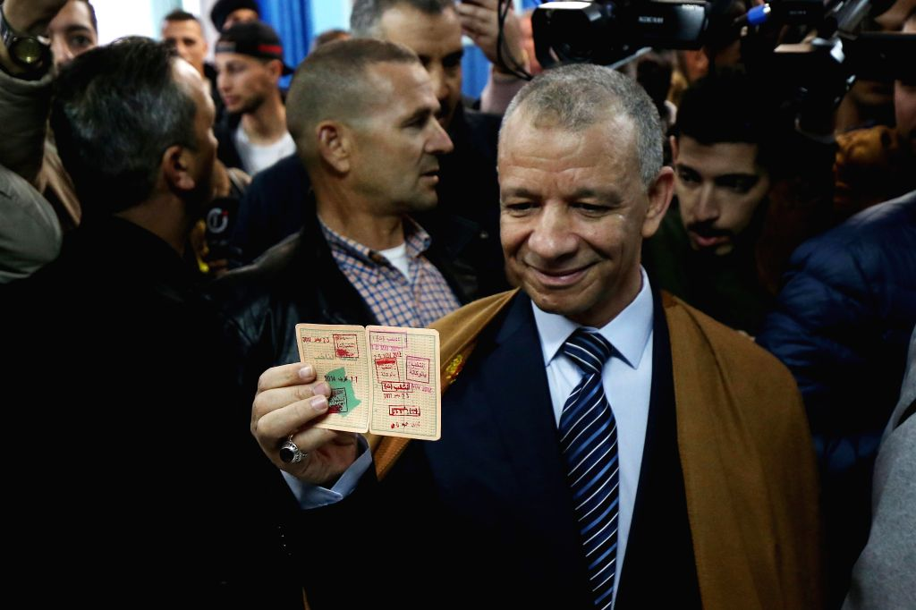 ALGIERS, Dec. 12, 2019 - Algerian presidential election candidate Abdelkader Bengrina (front) casts his vote at a polling station in Algiers, Algeria on Dec. 12, 2019. Algeria held presidential ...