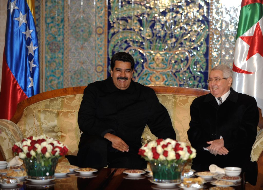 Venezuelan President Nicolas Maduro (L) is greeted by the upper parliament house speaker of Algeria Abdelkader Bensalah (R) upon his arrival at the airport of ...