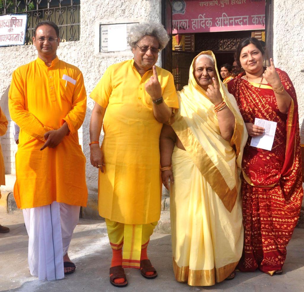 All World Gayatri Pariwar Head Pranav Pandya and Co-head of Shantikunj Shail Didi shows their inked finger after casting vote for Lok Sabha election at a polling station, in Haridwar, on ...