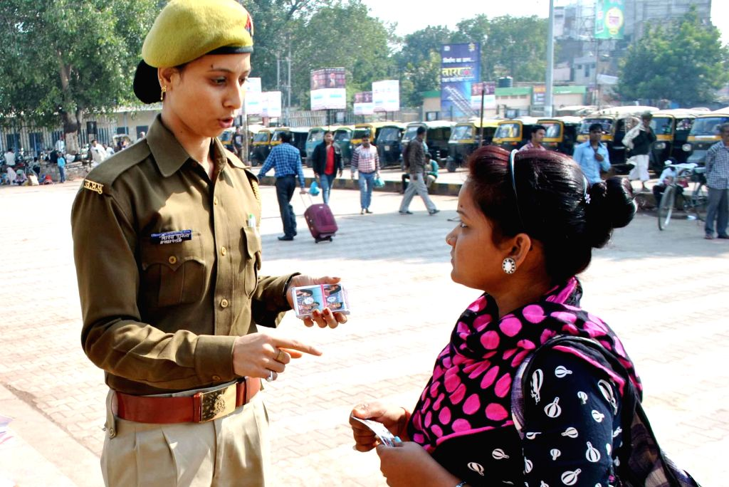 GRP personnel distribute Nirbhaya Card to a woman passenger at Allahabad railway junction on Nov 17, 2014.