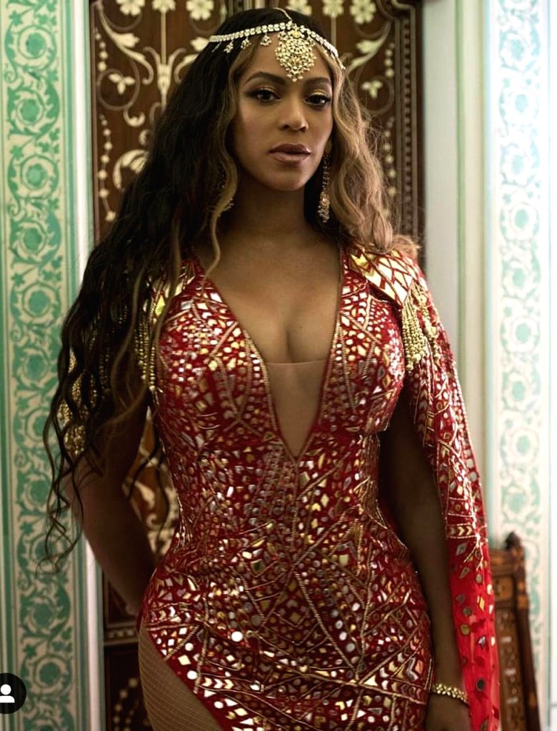 American singer-songwriter Beyonce wears a Red tulle Mirror sheet dress embellished with tiny mirror pieces and beads and an organza shoulder drape designed by Abu Jani Sandeep Khosla for Isha Ambani ... - Isha Ambani