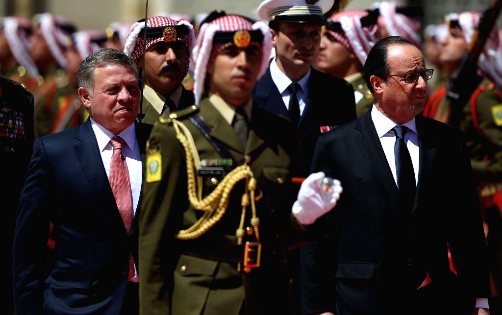 AMMAN, April 19, 2016 - Jordanian King Abdullah II (L) and French President Francois Hollande (R) review the guard of honor at the Royal Palace in Amman, Jordan, on April 19, 2016.