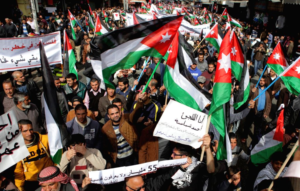 Jordanians protesters hold banners and wave Jordanian national flags during a march in Amman, capital of Jordan, on Feb. 14, 2014. About one thousand Jordanians from . - Abu Ghosh