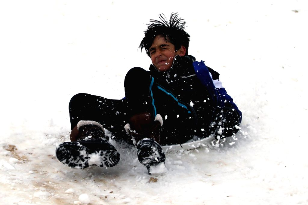 A boy play in the snow following a snowstorm in the Jordanian capital Amman on February 20, 2015. Blizzards dumped a blanket of snow over Israel, Jordan and ...