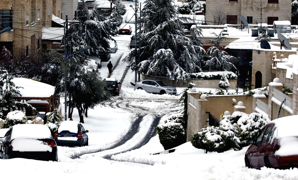 A man walks in a snow-covered street following a snowstorm in the Jordanian capital Amman on February 20, 2015. Blizzards dumped a blanket of snow over Israel, Jordan ...