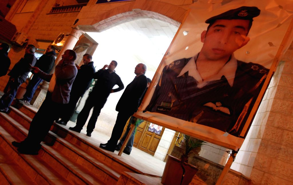 People stand by a poster of the Jordanian pilot Moaz al-Kasasbeh after the release of a video purportedly showing Islamic State captive Jordanian pilot being burnt ...