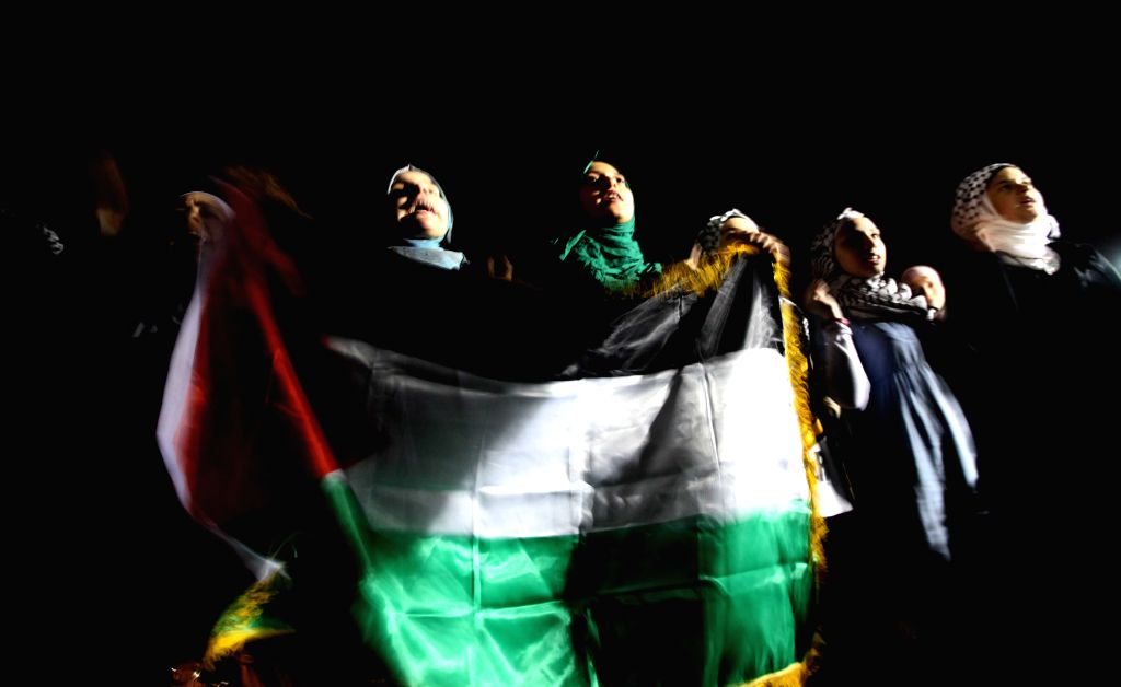 Protesters shout anti-Israel slogans during a demonstration calling for an end to Israeli air strikes in the Gaza Strip, near the Israeli embassy in Amman, Jordan, ...