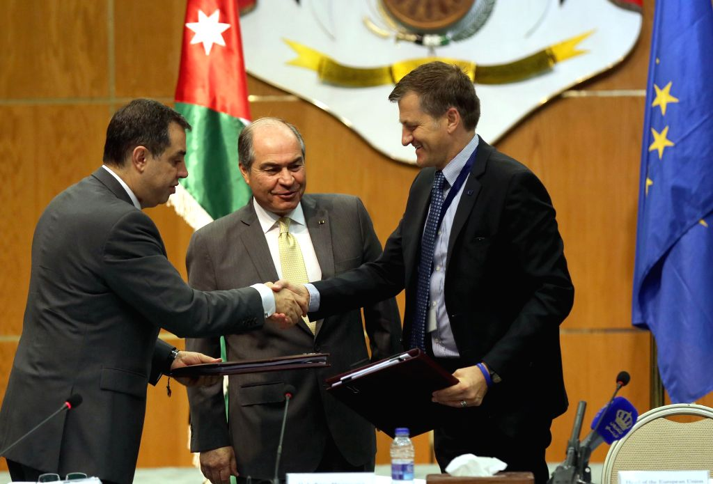 AMMAN, July 21, 2016 - EU Ambassador to Jordan Andrea Matteo Fontana (R) shakes hands with Jordanian Minister of Planning and International Cooperation Emad Fakhoury (L) after signing an agreement, ... - Hani Mulki