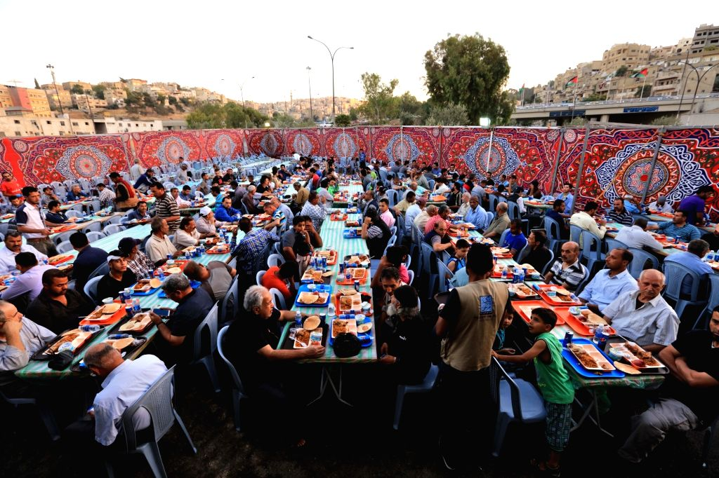 AMMAN, June 12, 2017 - Jordanians receive their meals at a charity banquet to break the fast during the holy fasting month of Ramadan in Amman, Jordan, on June 11, 2017.