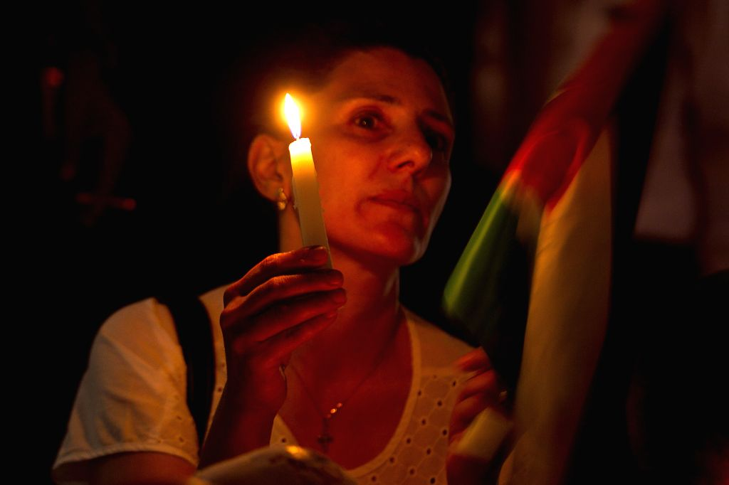 AMMAN, June 22, 2016 - A Jordanian woman holds a candle as she participates in a vigil for the victims of a terrorist attack at Jordan's border with Syria, in Amman June 21, 2016. A suicide attacker ...