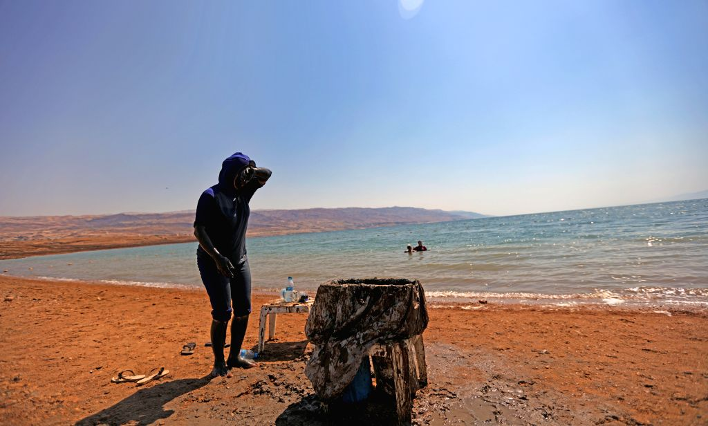 AMMAN, Sept. 15, 2016 - A tourist daubed with natural mud from the Dead Sea is seen on a beach of the Jordanian side of the Dead Sea, on Sept. 14, 2016.