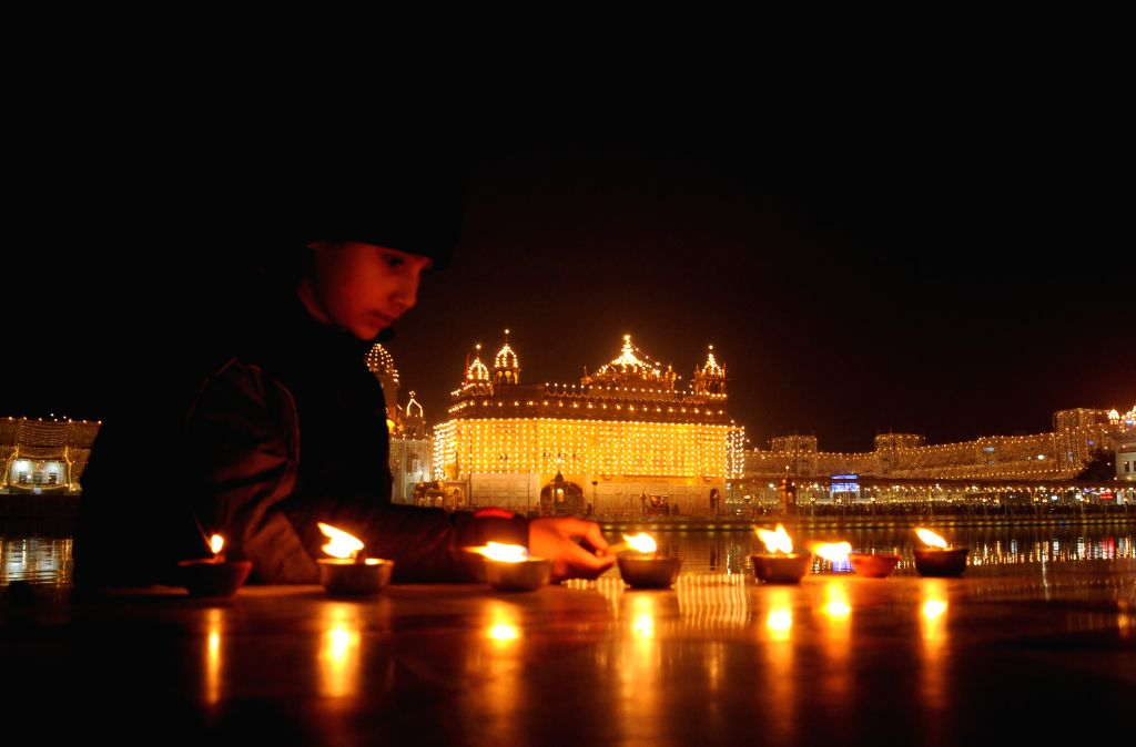 A child lights earthen lamps at the Golden Temple on the 350th birth anniversary of Guru Gobind Singh in Amritsar, on Dec 28, 2014.