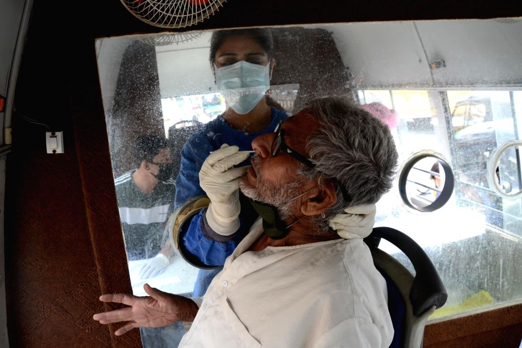 Amritsar: A health worker takes a nasal swab sample from a man for COVID-19 tests inside a mobile van, amid surge in coronavirus cases, in Amritsar On Friday, 23 April, 2021.(Photo:Pawan sharma/IANS)