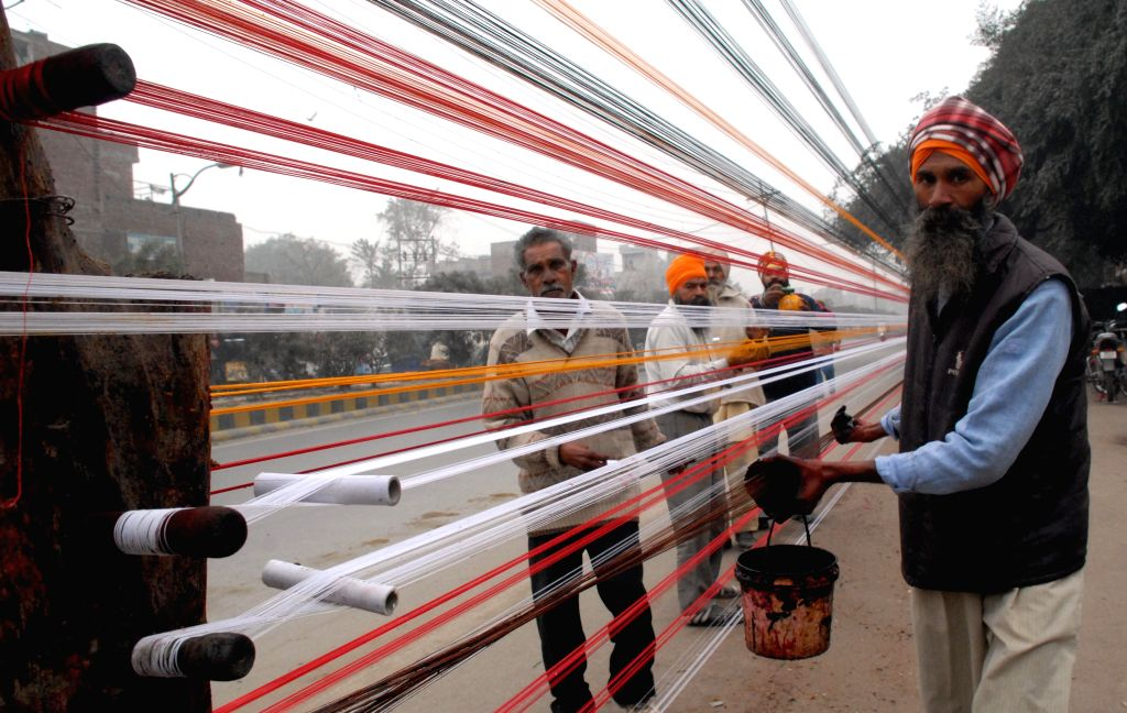 A man prepares `manja` - abrasive string, gummed, coloured and coated with powdered glass for fighter kites - ahead of Lohri in Amritsar, on Jan 10, 2015.