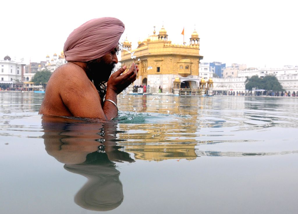 A Sikh devotee takes holy dip on Makar Sankranti at the Golden Temple in Amritsar on Jan 14, 2015.