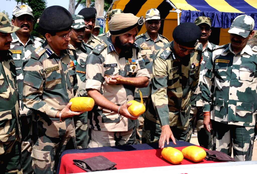 : Amritsar: Border Security Force (BSF) officers present before press around four kg heroin and other items recovered from a drug smuggler near the Border Out Post (BOP) Ramkot, some 36 km from ...