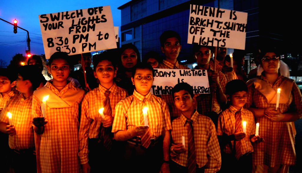 Childrens hold a candlelight vigil to celebrate the `Earth Hour` at Amritsar on March 28, 2015.