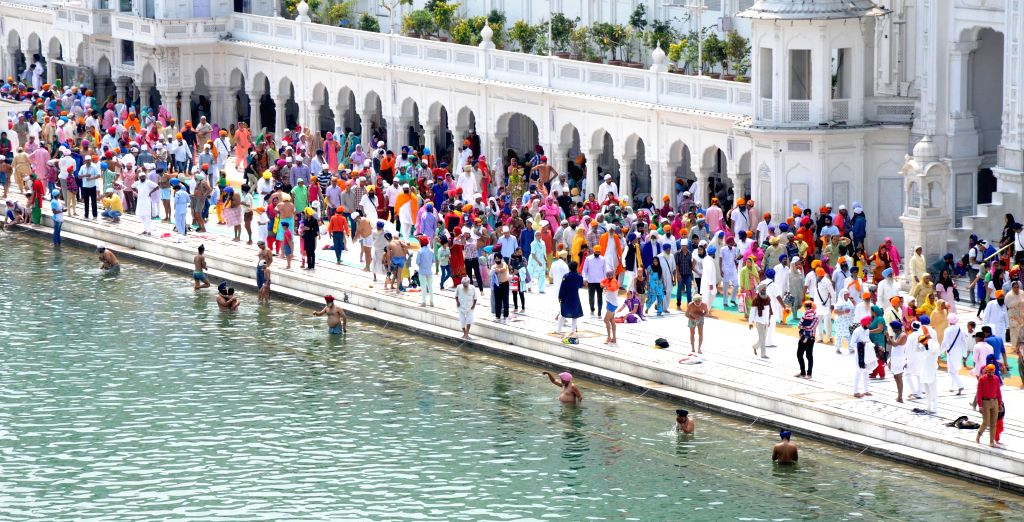 Devotees take bath in holy Sarover and pay obeisance at Golden Temple on the occasion of Baisakhi festival in Amritsar on April 14, 2015.