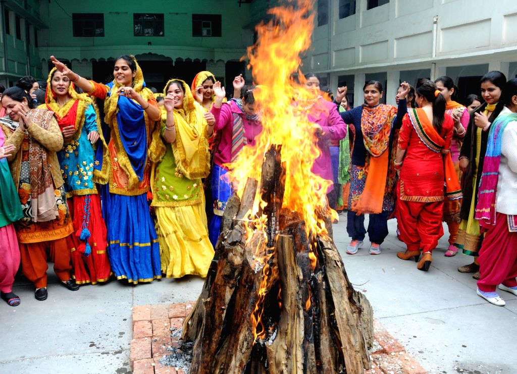 Girls wearing traditional Punjabi dresses celebrate Lohri in Amritsar on Jan 13, 2015.