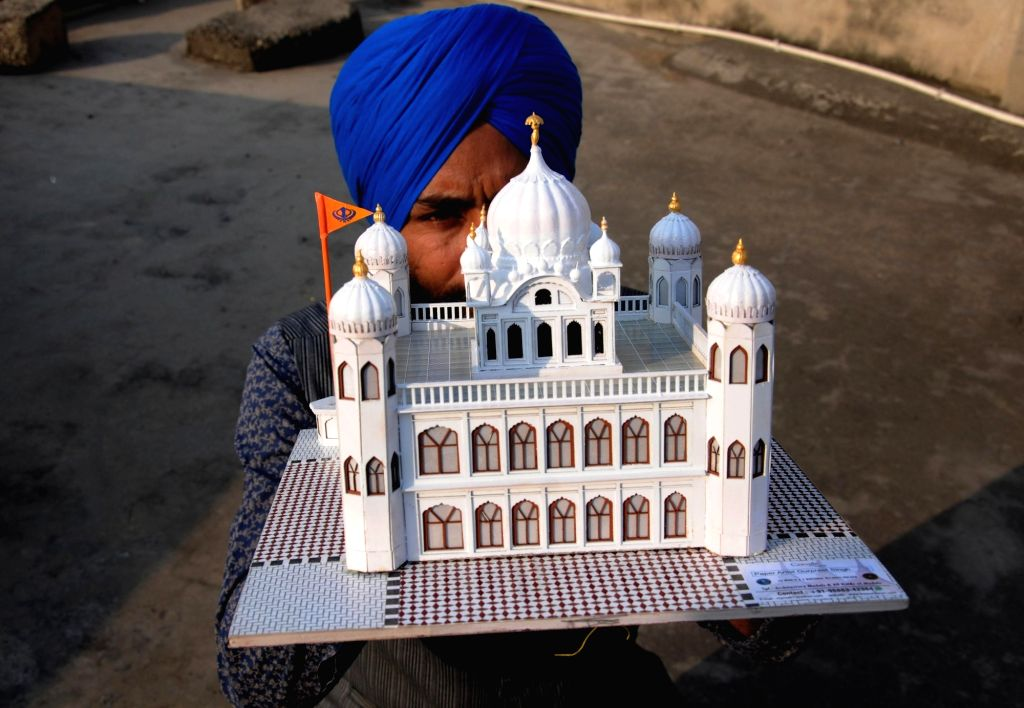Amritsar: Paper artist Gurpreet Singh shows a model of Kartarpur Sahib, the final resting place of Guru Nank Dev, created by him, on the eve of the first Sikh Guru's birth anniversary, in Amritsar on Nov 22, 2018. (Photo: IANS) - Gurpreet Singh and Nank Dev